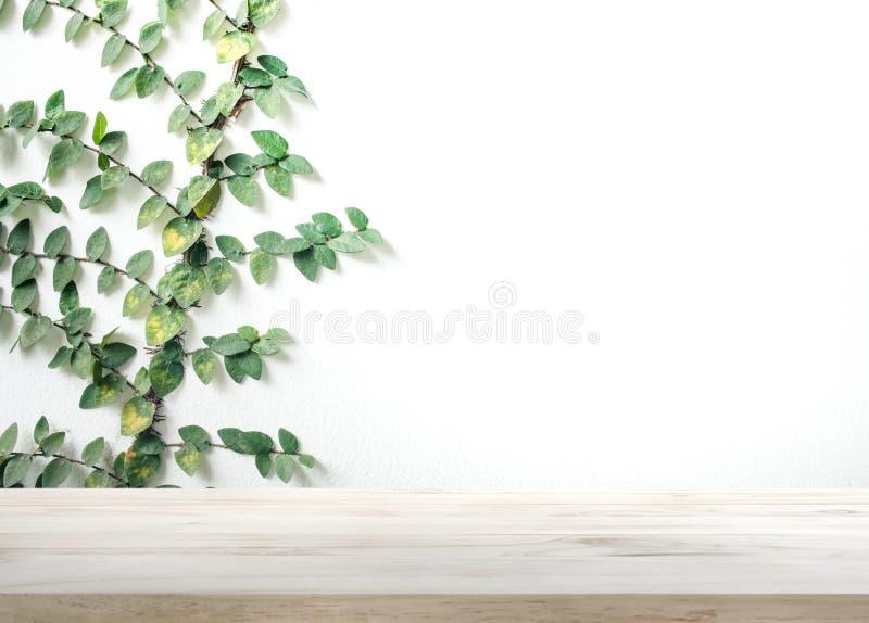 在白色墙壁上的木台式有叶子背景 库存图片