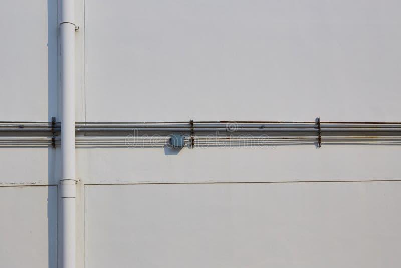 在白色墙壁上的白色管和钢管 库存图片