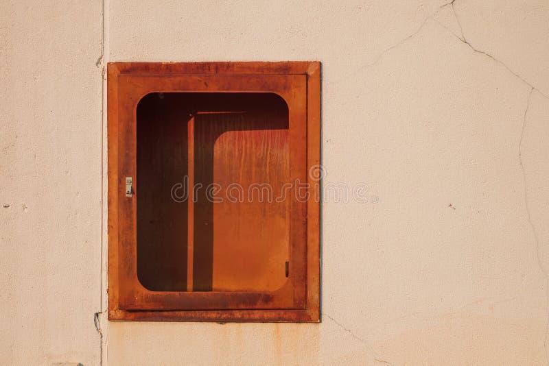 在白色墙壁上的老红火灭火器 免版税库存图片