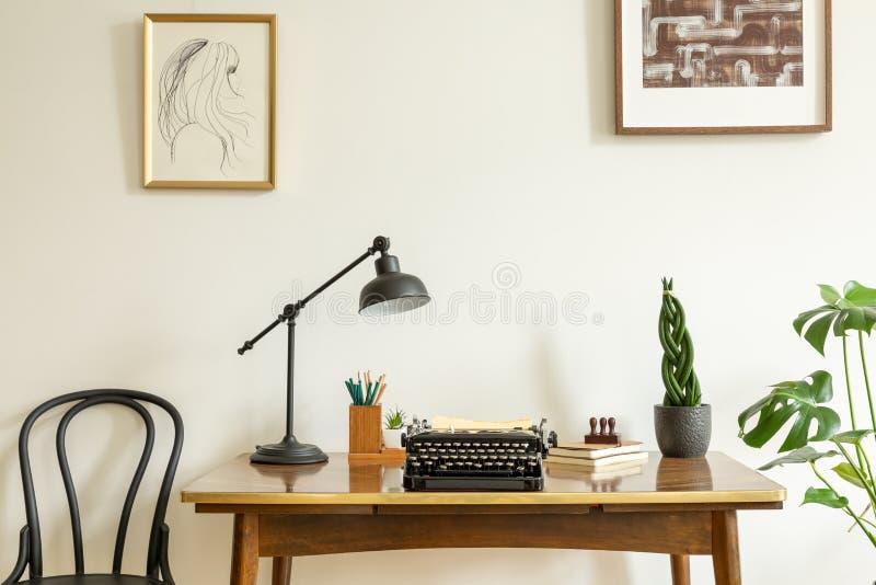 在白色墙壁上的被构筑的图画在古董上,有葡萄酒的木书桌,在家庭办公室内部的黑打字机 库存图片