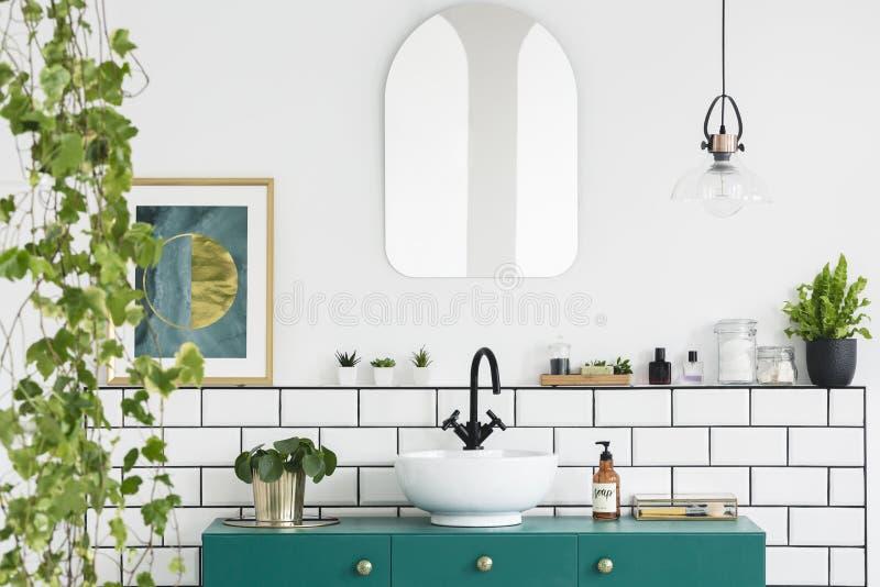 在白色墙壁上的镜子在卫生间内部的绿色水盆上与植物和海报 实际照片 免版税库存图片