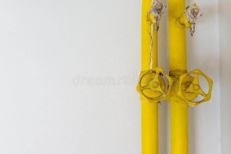 在白色墙壁上的黄色管子 库存照片