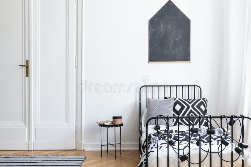 在白色墙壁上的黑海报在简单的卧室内部的床上与门和桌 免版税库存照片