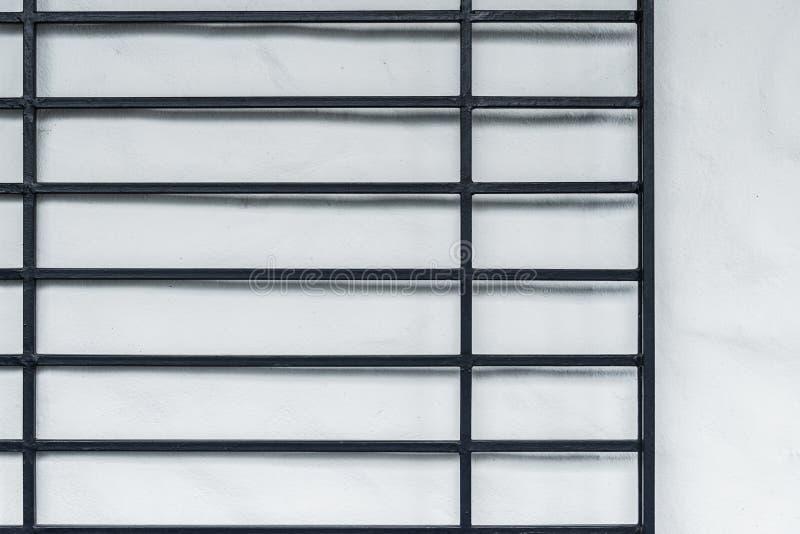 在白色墙壁上的黑铁篱芭 库存照片