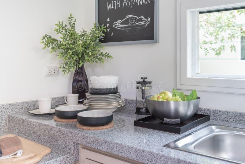 在白色墙壁上的黑人委员会在有器物的现代厨房室 免版税图库摄影