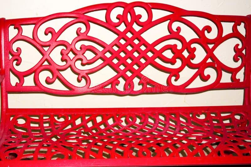 在白色墙壁上隔绝的红色长凳 免版税库存图片