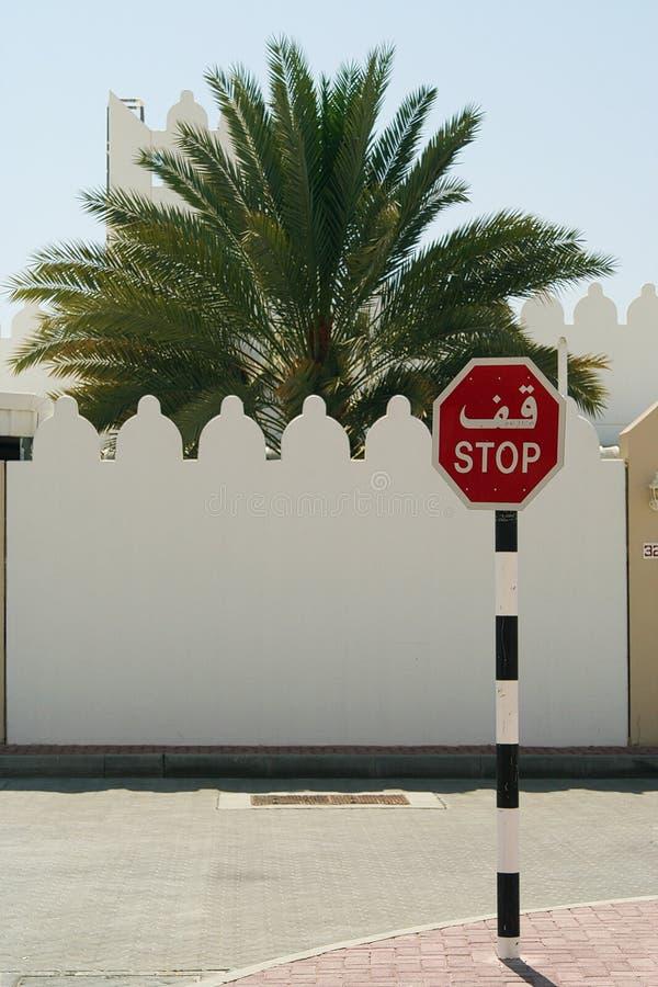 在白色墙壁前面的停车牌有城垛和棕榈树的,阿曼 库存照片