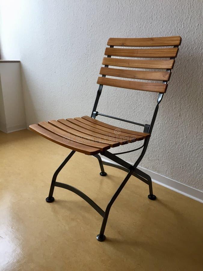在白色墙壁的空的可折叠椅子 库存照片