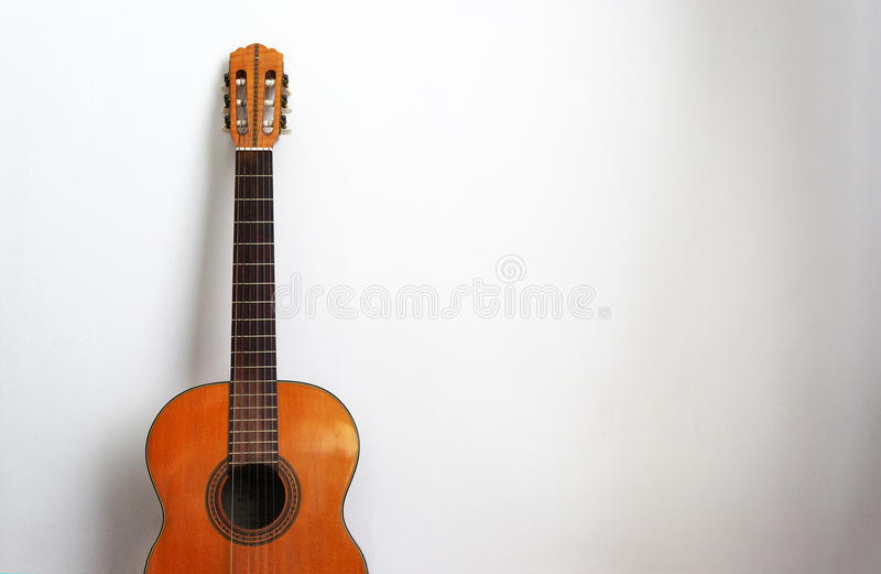 在白色墙壁背景的声学吉他 免版税库存图片
