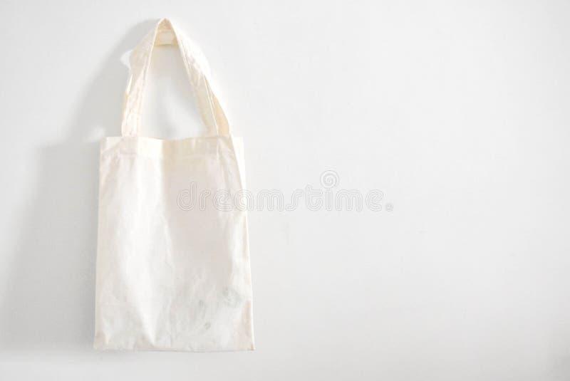 在白色墙壁背景的白色布料袋子 免版税库存照片