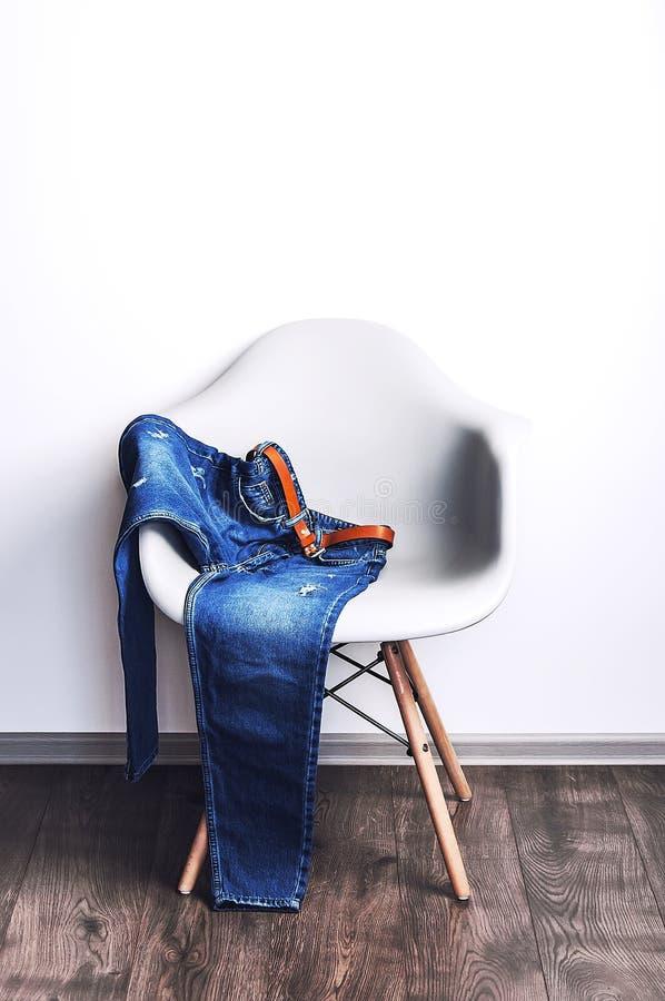 在白色墙壁背景的设计师塑料椅子 在椅子的蓝色牛仔裤 库存照片