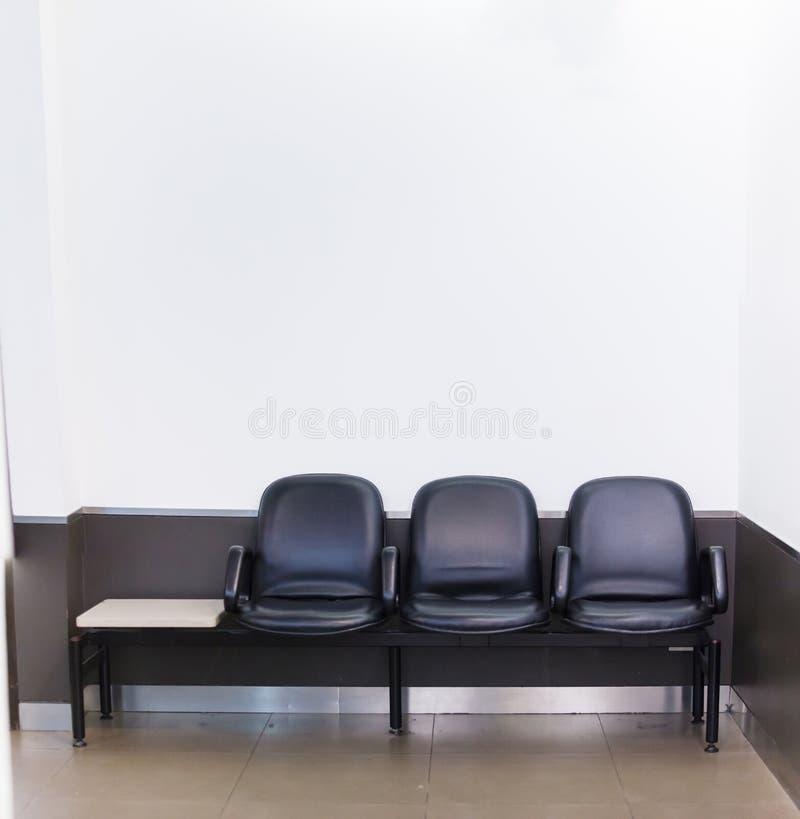 在白色墙壁背景的黑皮革前座统排椅行在等候室 建筑家或办公室内部,议院家具, 免版税库存图片