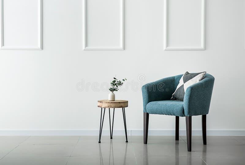 在白色墙壁附近的软的扶手椅子在客厅内部  库存照片
