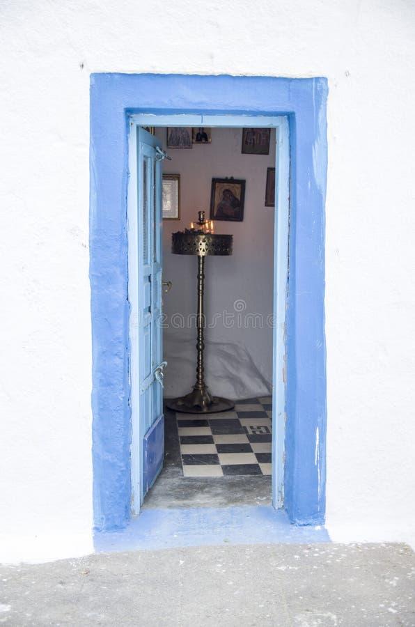 在白色墙壁, santorini上的老蓝色木开放教会门 库存图片