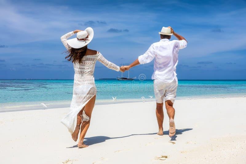 在白色夏天衣裳跑的夫妇愉快在一个热带海滩 库存图片