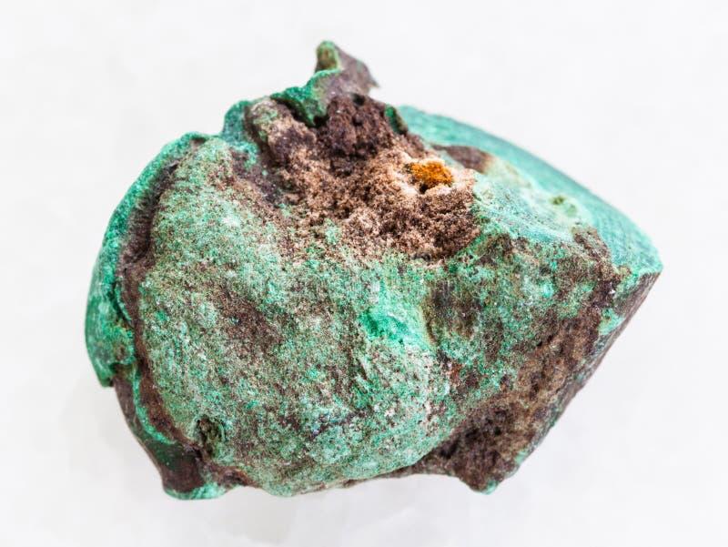 在白色大理石的粗砺的绿沸铜石头 免版税库存图片