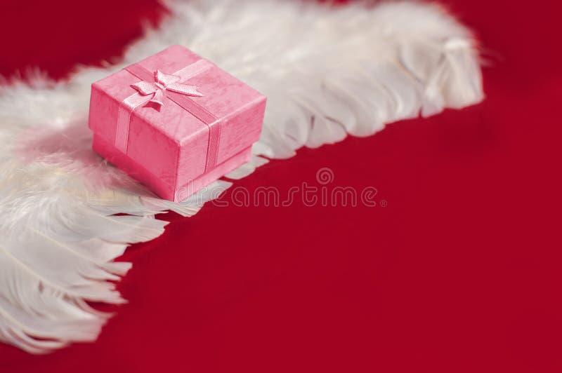 在白色天使羽毛翼的红色礼物盒 库存图片