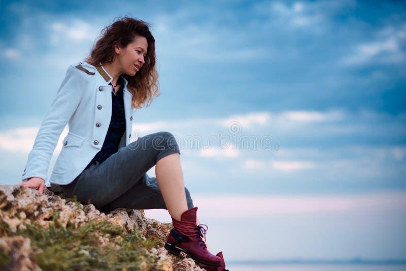 在白色夹克和宽长裤打扮的时兴的女孩摆在日落天空背景,坐石头 库存照片