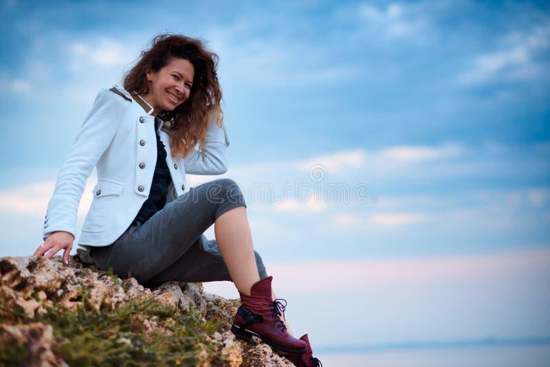 在白色夹克和宽长裤打扮的时兴的女孩摆在日落天空背景,坐石头 免版税库存照片