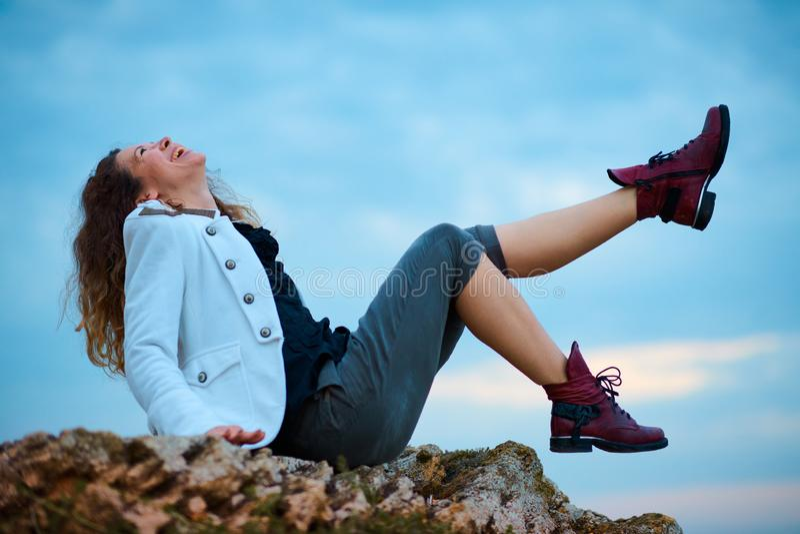 在白色夹克和宽长裤打扮的时兴的女孩摆在日落天空背景,坐石头 免版税库存图片