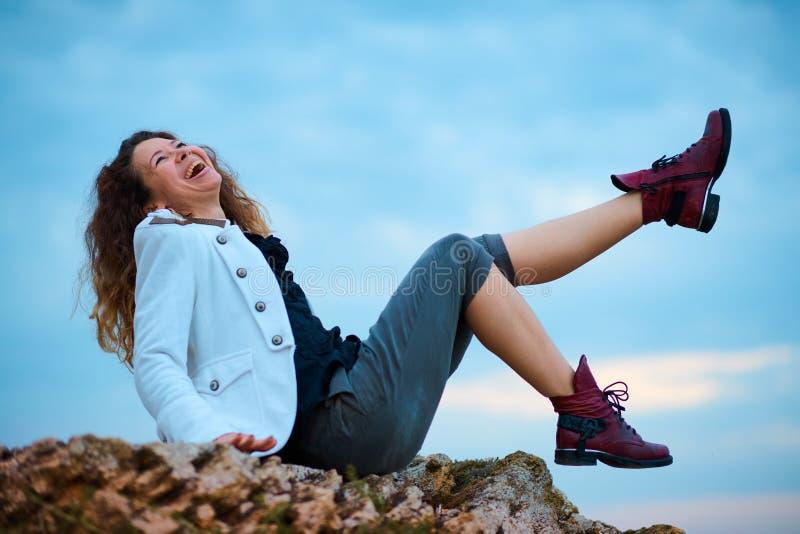 在白色夹克和宽长裤打扮的时兴的女孩摆在日落天空背景,坐石头 图库摄影