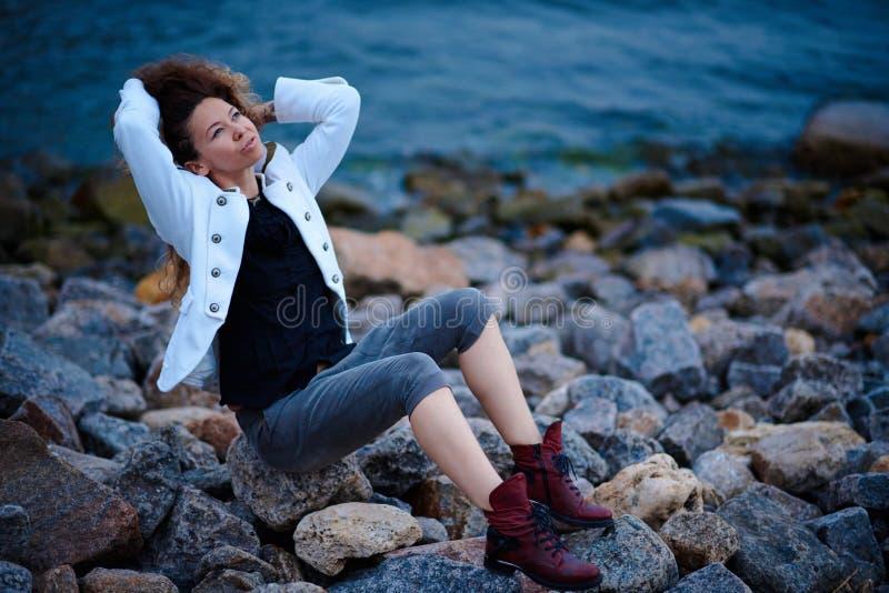 在白色夹克和宽长裤打扮的时兴的女孩摆在海附近在晚上 免版税库存图片