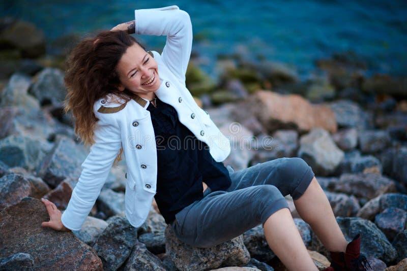 在白色夹克和宽长裤打扮的时兴的女孩摆在海附近在晚上 免版税库存照片