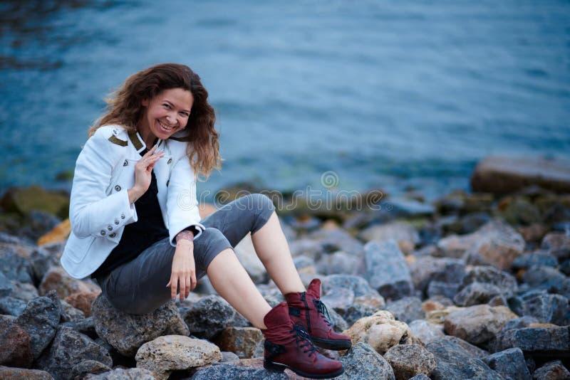 在白色夹克和宽长裤打扮的时兴的女孩摆在海附近在晚上 免版税图库摄影