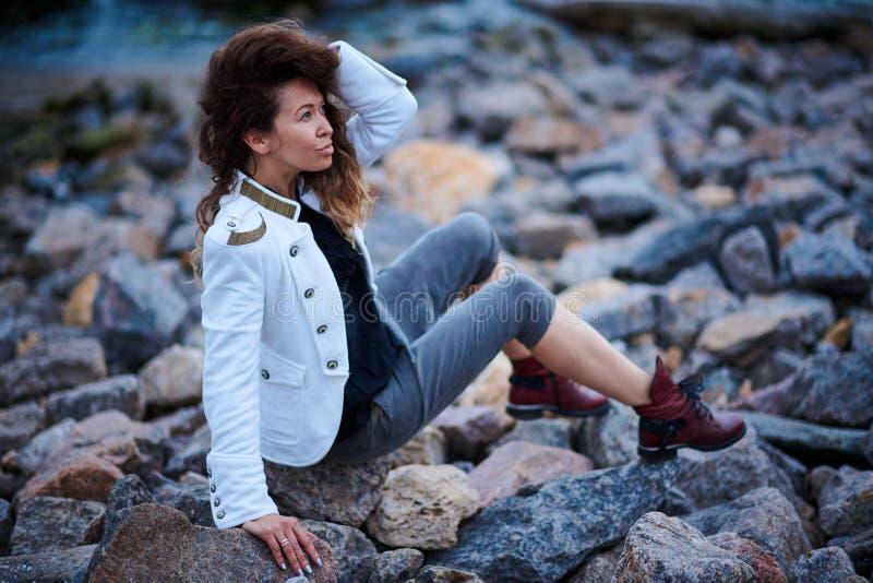 在白色夹克和宽长裤打扮的时兴的女孩摆在海附近在晚上 图库摄影
