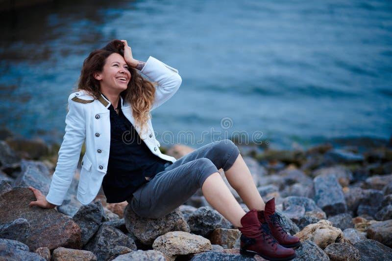 在白色夹克和宽长裤打扮的时兴的女孩摆在海附近在晚上 库存照片