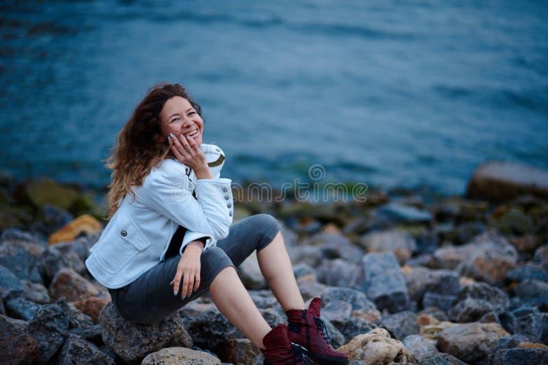 在白色夹克和宽长裤打扮的时兴的女孩摆在海附近在晚上 库存图片