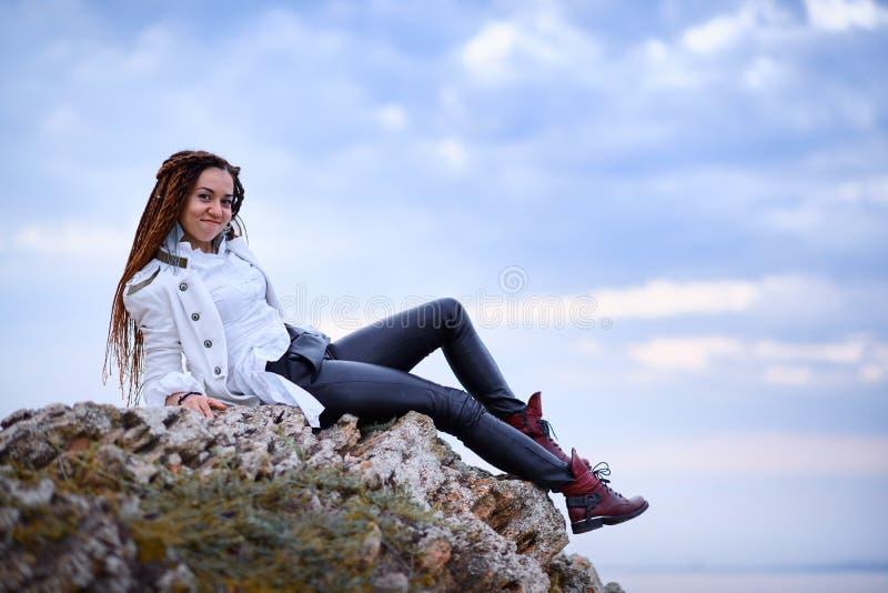 在白色夹克和黑皮革长裤打扮的Dreadlocks时兴的女孩摆在海附近在晚上 免版税库存照片