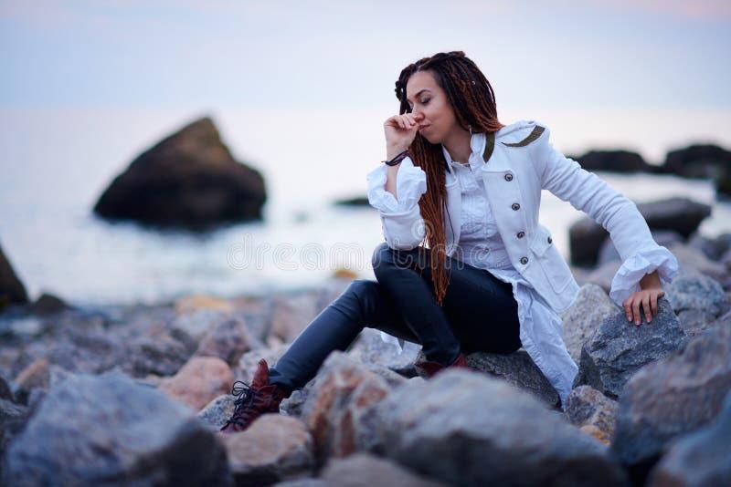 在白色夹克和黑皮革长裤打扮的Dreadlocks时兴的女孩摆在海附近在晚上 免版税库存图片