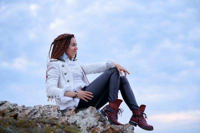 在白色夹克和黑皮革长裤打扮的Dreadlocks时兴的女孩摆在海附近在晚上 库存照片