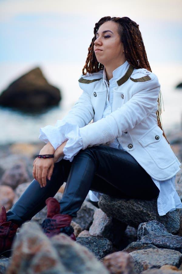 在白色夹克和黑皮革长裤打扮的Dreadlocks时兴的女孩摆在海附近在晚上 免版税图库摄影
