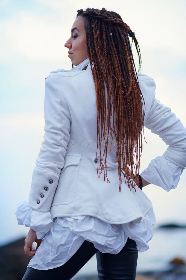 在白色夹克和黑皮革长裤打扮的Dreadlocks时兴的女孩摆在海附近在晚上 库存图片