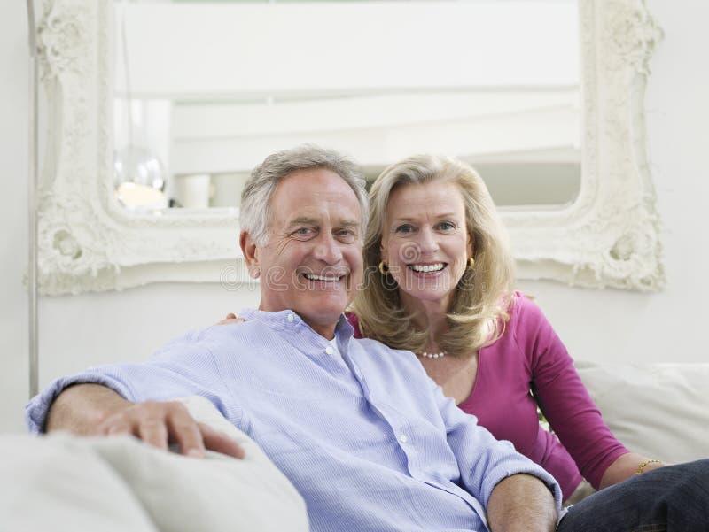 在白色家庭内部的微笑的成熟夫妇 库存图片