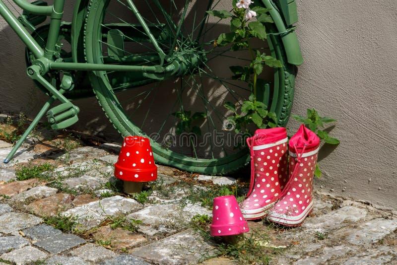 在白色小点的儿童的红色胶靴在老城市的铺路石站立在a的一辆绿色葡萄酒装饰自行车附近 免版税库存照片