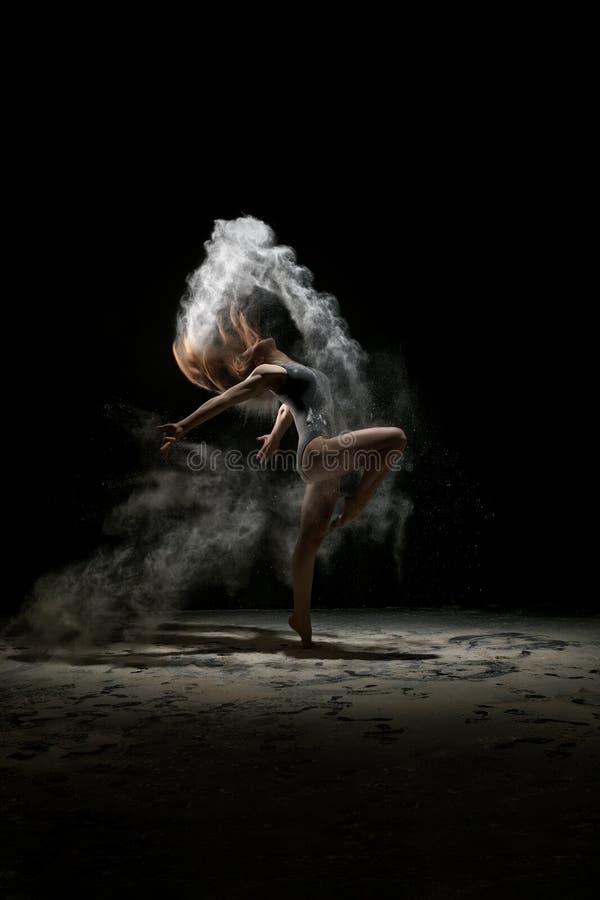 在白色尘土演播室画象云彩的女孩跳舞  图库摄影
