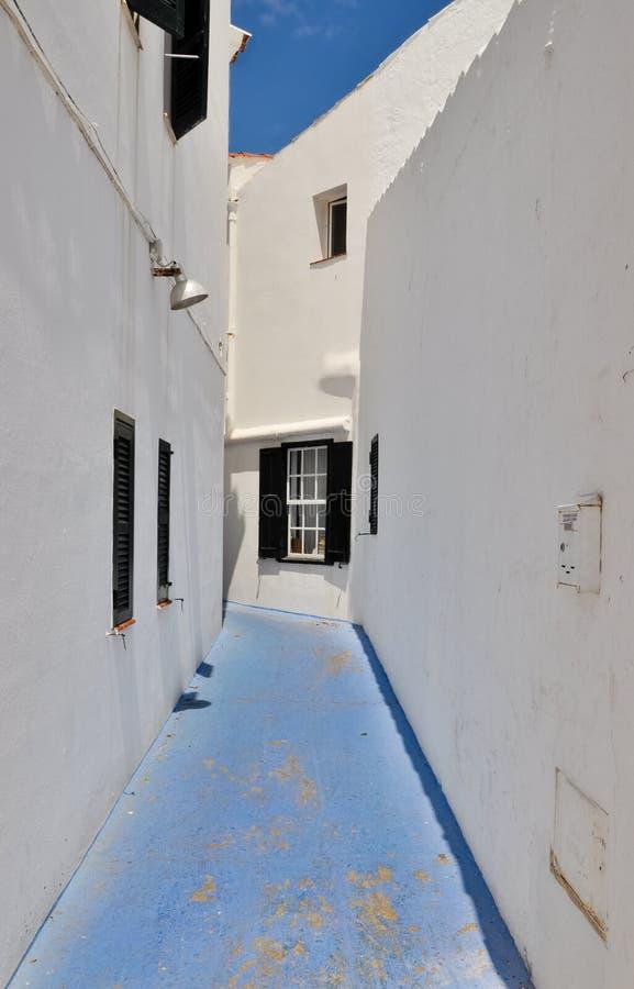 在白色房子之间的蓝色街道,梅诺卡岛,西班牙 库存照片