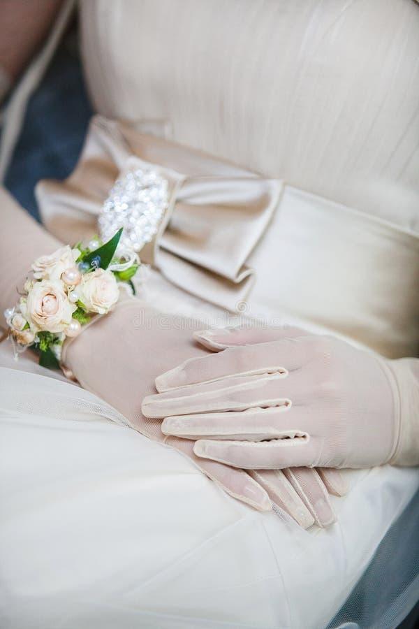 在白色手套和镯子的典雅的新娘手 免版税库存照片