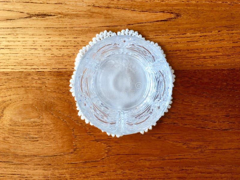 在白色手工制造钩针编织鞋带盘子上把放的透明盘 库存照片