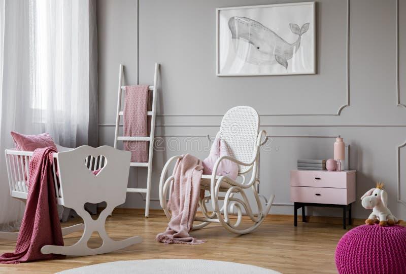 在白色摇椅的粉红彩笔毯子在与摇篮、斯堪的纳维亚梯子和nightstand的宽敞婴孩室内部 库存照片