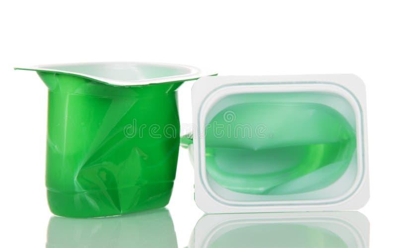 在白色有酸奶关闭的空的塑料杯子隔绝的 免版税库存图片