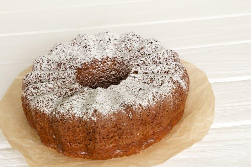 在白色木书桌上的自创香草腹网蛋糕 免版税库存照片