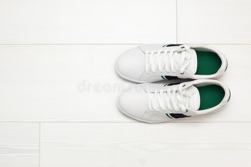 在白色木地板上的白色运动鞋 免版税库存照片
