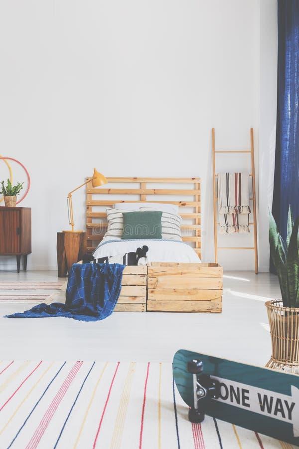 在白色木床上的绿色枕头与在时髦的卧室内部,与拷贝空间的真正的照片的床头板 免版税库存照片