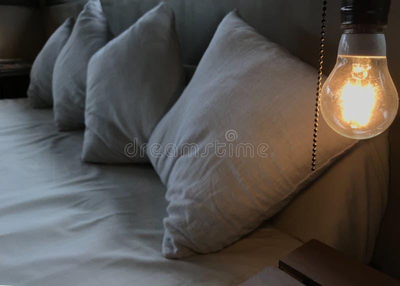 在白色木床的头的温暖的桔子发光的白炽光电灯泡 向高处发射室内设计,舒适并且放松 库存照片
