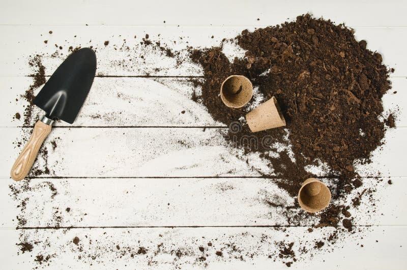 在白色木板条背景的园艺工具顶视图 图库摄影