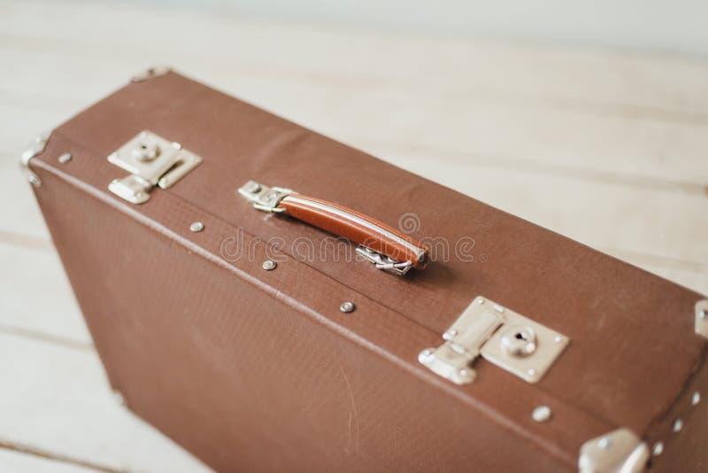 在白色木板走道地板上的老棕色手提箱 库存图片